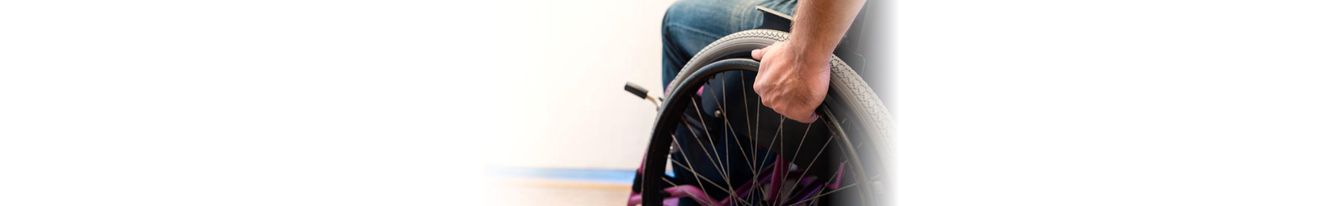 person holding to the wheel of a wheelchair